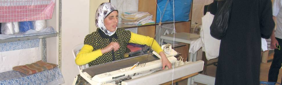 Young woman sitting at knitting machine