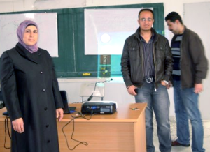 Three people standing in classroom